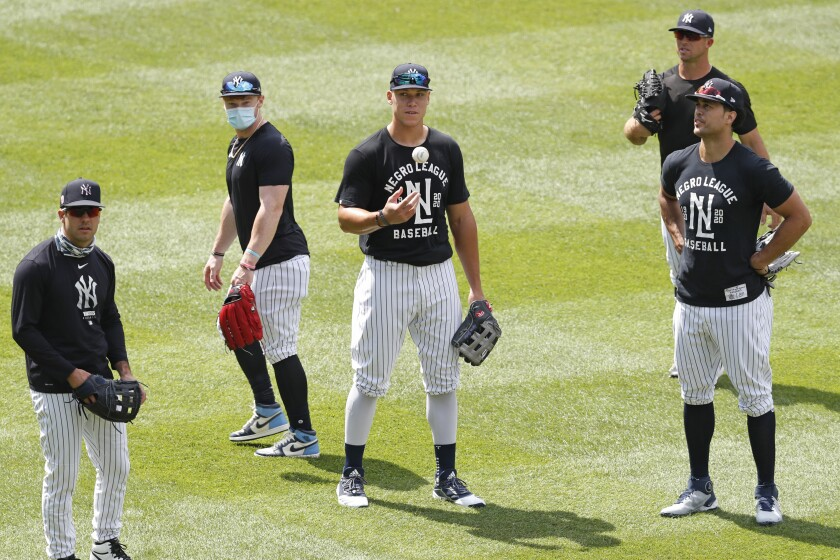 New York Yankees outfielders from left, Mike Tauchman, Clint Frazier, Aaron Judge, Brett Gardner, above right, Giancarlo Stanton, far right stand in the outfield during a workout at the Yankees summer baseball training camp, Wednesday, July 15, 2020, at Yankee Stadium in New York. (AP Photo/Kathy Willens)