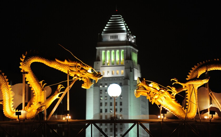 Los Angeles City Hall is bordered by statues of dragons in a view from Chinatown.