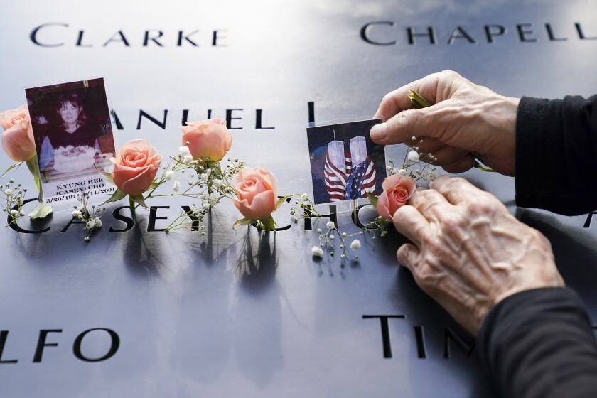 Mourners place flowers and pictures at the National September 11 Memorial and Museum