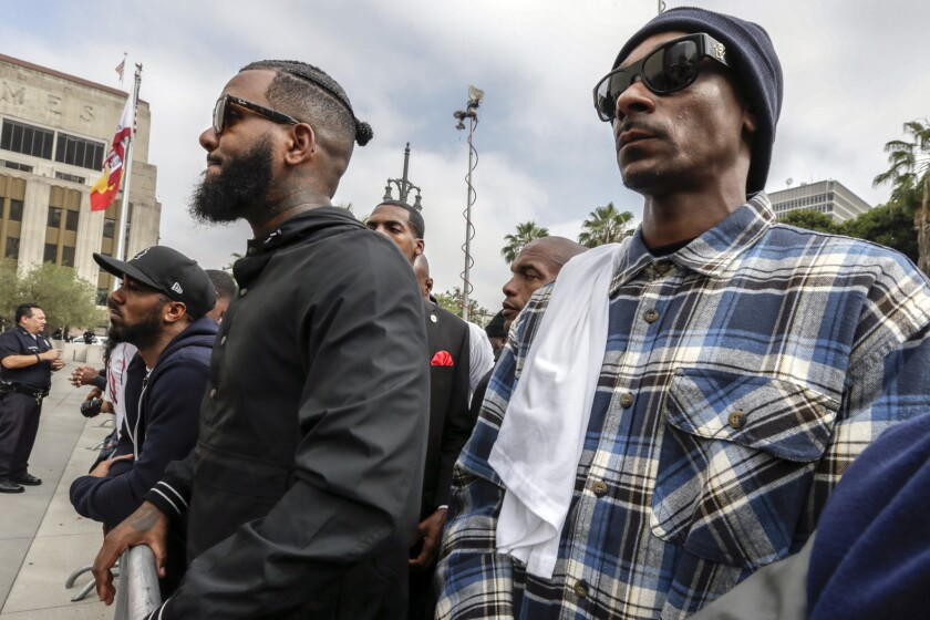Rappers the Game, left, and Snoop Dogg stand outside LAPD headquarters during a peaceful march earlier this month.