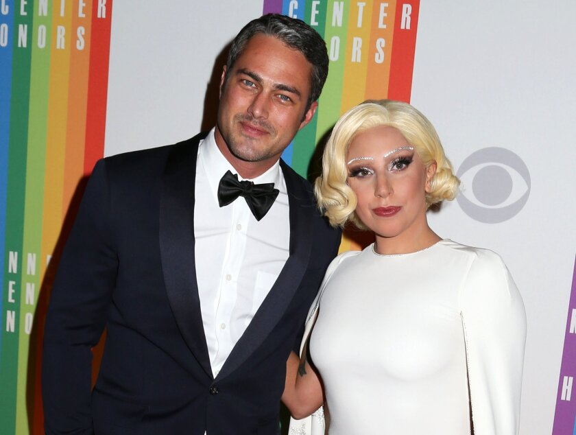 """In this Dec. 7, 2014 file photo, Taylor Kinney and Lady Gaga attend the 37th Annual Kennedy Center Honors in Washington. Lady Gaga announced on her Instagram account Monday that she and Kinney are engaged. Kinney stars in the NBC series """"Chicago Fire."""" (Photo by Greg Allen/Invision/AP, File)"""