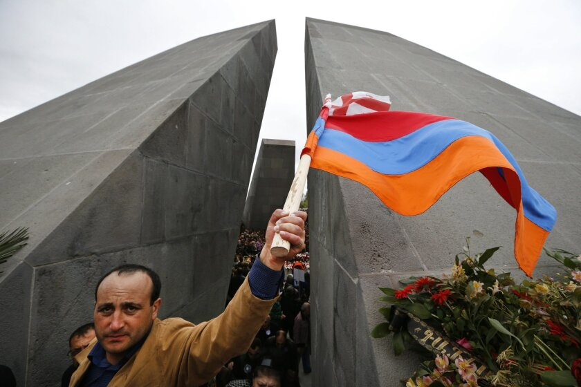 A man waves Armenian and Georgian flags at a memorial to Armenians killed by the Ottoman Turks, during marking the centenary of the mass killings, in Yerevan, Armenia, Friday, April 24, 2015. Armenians on Friday mark the centenary of what historians estimate to be the slaughter of up to 1.5 million