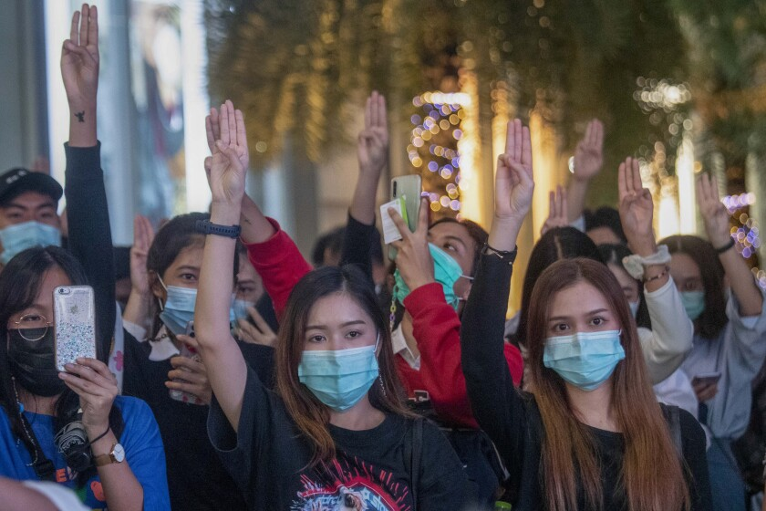 Pro-democracy activists flash three-fingered salutes during a rally outside Siam Paragon, one of the largest shopping malls, in Bangkok, Thailand, Tuesday, Oct. 20, 2020. Thailand's Cabinet on Tuesday approved a request to recall Parliament for a special session to deal with the political pressures from ongoing anti-government protests. The Cabinet at its weekly meeting approved the request, which calls for a non-voting session on Oct. 26-27. (AP Photo/Sakchai Lalit)