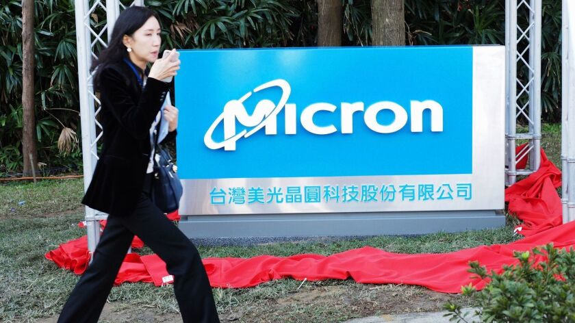 A woman walks past the a Micron Technology sign in Taiwan in 2016. The company said Tuesday that it had started shipping some components to Huawei after its lawyers studied export restrictions.