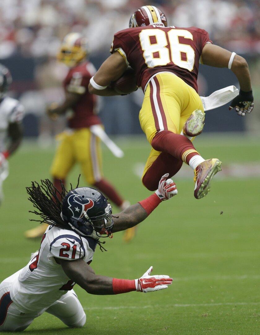Houston Texans' Kendrick Lewis (21) trips up Washington Redskins' Jordan Reed (86) during the first quarter of an NFL football game Sunday, Sept. 7, 2014, in Houston. (AP Photo/David J. Phillip)