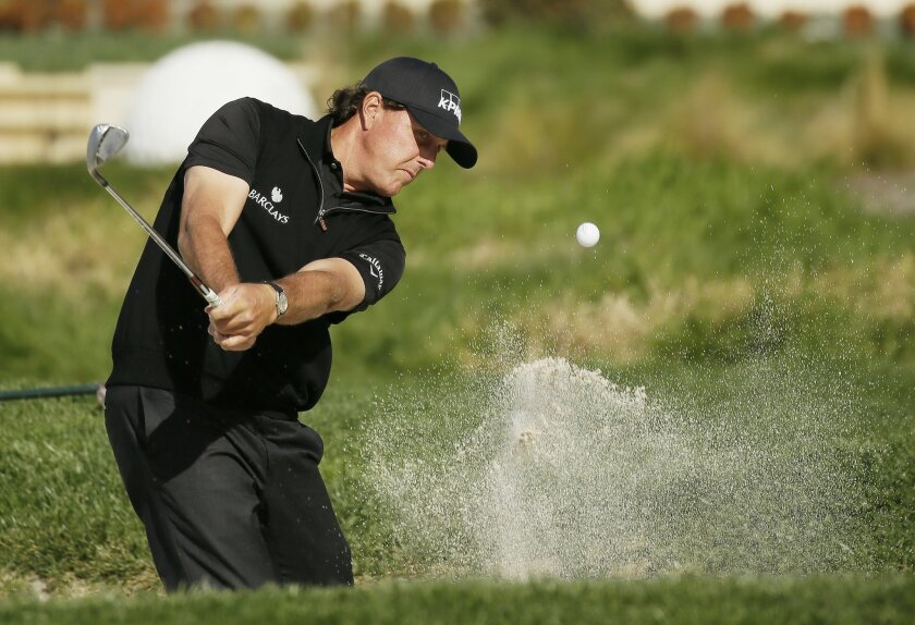 Phil Mickelson hits out of a bunker onto the second green of the Pebble Beach Golf Links during the final round of the AT&T Pebble Beach National Pro-Am golf tournament Sunday, Feb. 14, 2016, in Pebble Beach, Calif. (AP Photo/Eric Risberg)