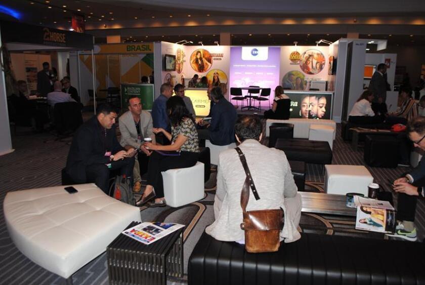 Asistentes a la feria de la Asociación Nacional de Ejecutivos de Programas de Televisión (Natpe) conversan durante el primer día hoy en Miami, Florida. EFE