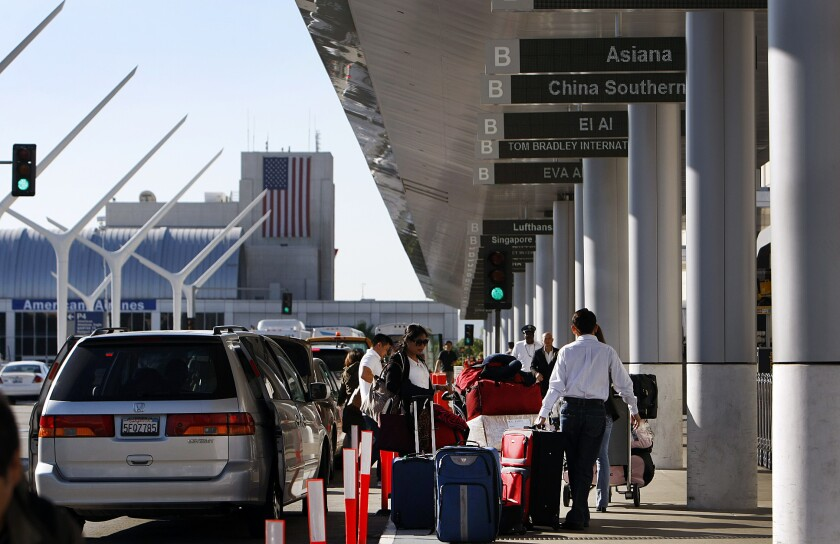 Travelers arrive at the Tom Bradley International Terminal at LAX on Oct. 15 after a bottle with dry ice exploded earlier that morning.