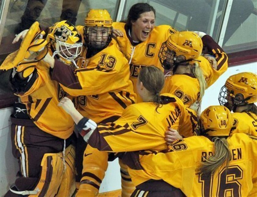 In this March 9, 2013 photo, Minnesota goalie Noora Raty, left, is congratulated by teammates including Milica McMillen (13) after winning the WCHA championship game, 2-0, against North Dakota in Minneapolis. Not only has the Minnesota women's hockey team not lost in 46 consecutive games, the Gophe