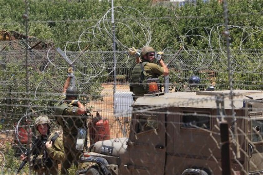 Israeli soldiers performing maintenance on the border wire fence, near the Lebanese-Israeli border village of Kfar Kila, on Friday June 3, 2011. Palestinian organizers of a march to the border with Israel planned for later this week say they have canceled the action. The cancellation comes after Lebanese authorities declared the area around the shared border with Israel a closed military zone in an attempt to prevent the border march. (AP Photo/Mohammed Zaatari)