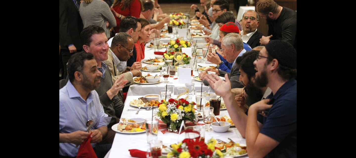Daniel Orth, second from left, and Khalid Alexander, right, have a conversation as they and others eat together during the Islamic Center of San Diego 2018 Interfaith Iftar.