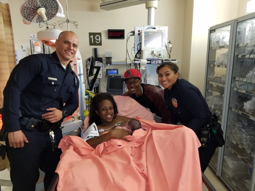 LAPD Officers Brian Armendariz and Maraea Toomalatai pose with Sasha Murphy and Mohammed Tindley, whom they had pulled over for speeding and then escorted to the hospital.
