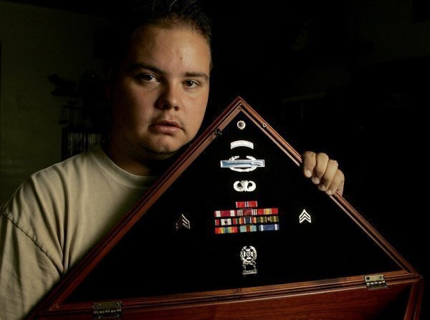 Gordon Treber Jr. holds a shadow box and wears a bracelet for his only brother, Sgt. James M. Treber, who was killed in Afghanistan in June 2008. The Treber brothers grew up in Imperial Beach. This photo was taken in July 2008.