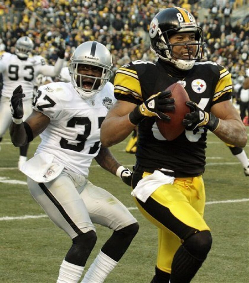 Pittsburgh Steelers receiver Hines Ward, right, scores in front of Oakland Raiders' Chris Johnson (27) after taking a pass from Steelers quarterback during the fourth quarter of an NFL football game in Pittsburgh, Sunday, Dec. 6, 2009. The Raiders won 27-24. (AP Photo/Gene J. Puskar)
