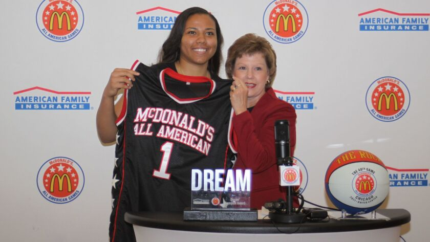 Destiny Littleton receives a commemorative jersey from San Diego County McDonald's representative Gale Nickerson.