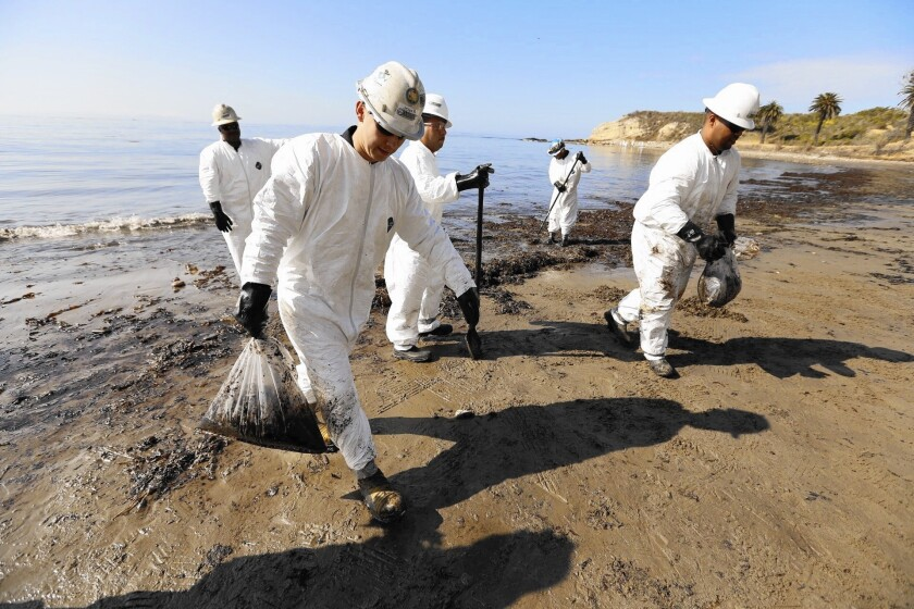 Cleanup crews bag oiled sand at Refugio State Beach in 2015.