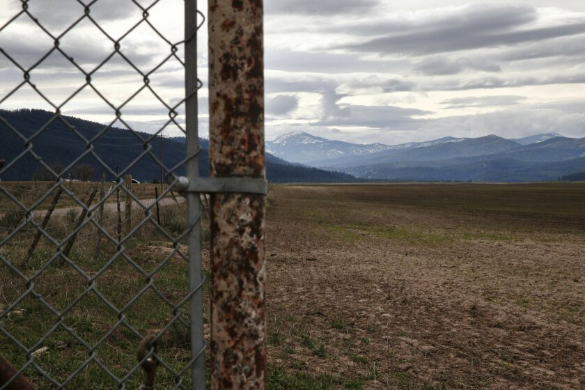 In this April 12, 2016 photo, mountains rise behind a fence on land belonging to Gloria Roark, a vocal opponent of refugees coming to her state, near Clearwater, Mont. What started as a disagreement over whether to welcome dozens of refugees to this corner of western Montana soon erupted into somet
