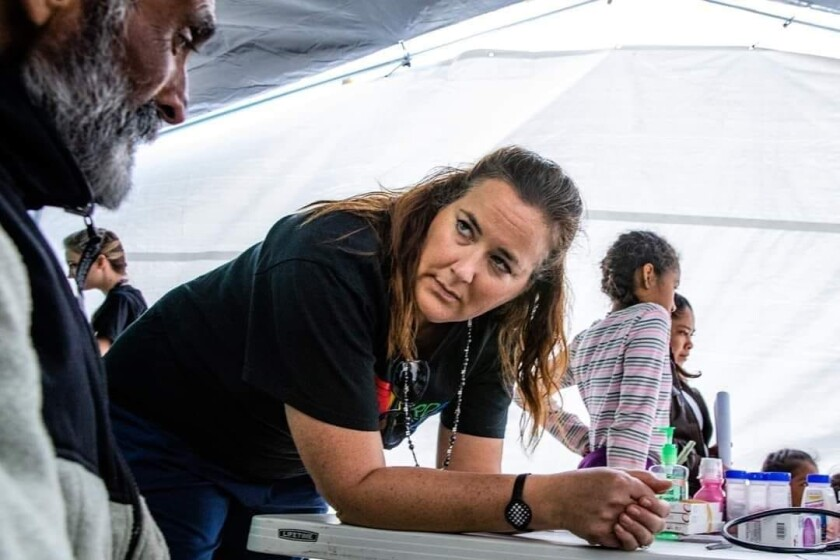 Courtesy photo. Courtesy of Dr. Julie Sierra and Photographer Hal Myers. San Diego area doctor Julie Sierra speaks with a patient during a free mobile clinic she volunteers at to help provide health care to migrants in Tijuana.