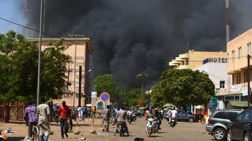 People watch black smoke rising during attacks on Burkina Faso's capital, Ouagadougou, on March 2.