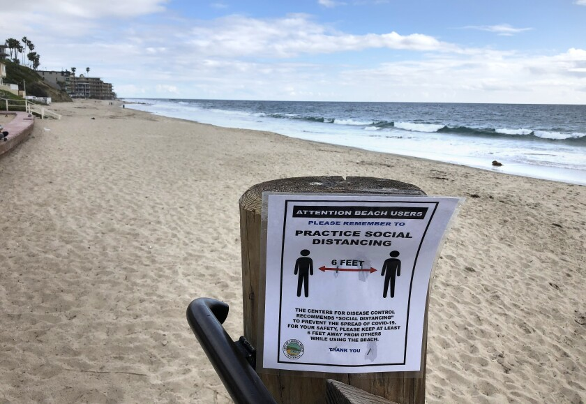 A sign emphasizing social distancing on a beach