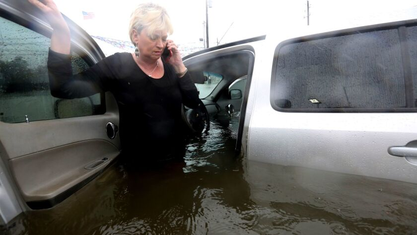 Rhonda Worthington talks on her cellphone with a 911 dispatcher after her car became stuck in rising
