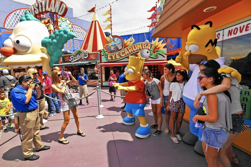 """Bart and Homer, characters from the popular television program """"The Simpsons,"""" interact with guests at Universal Studios Hollywood theme park."""