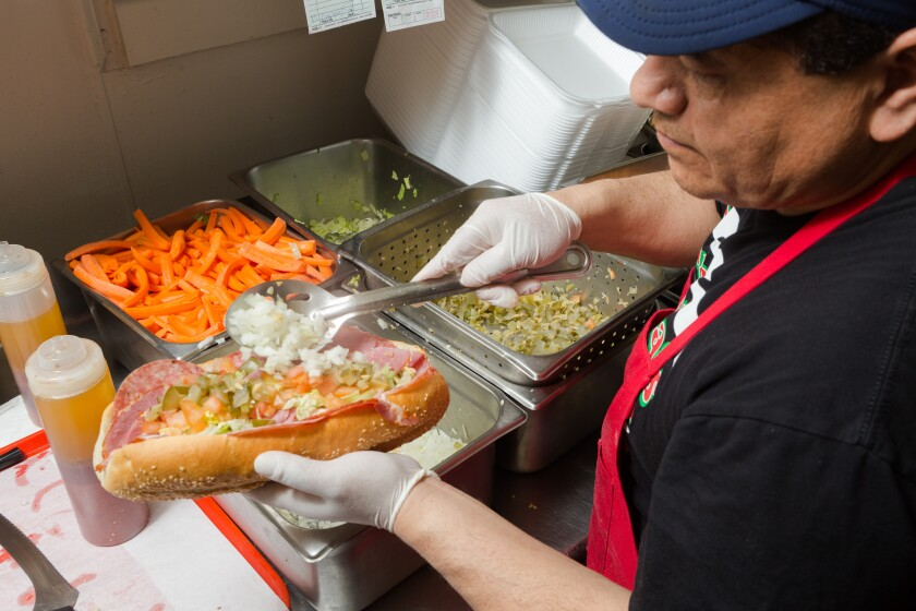 Marcelo Bizarro makes a Mr. G's sandwich at Giamela's.