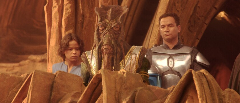 "Bounty hunter Jango Fett (Temuera Morrison) with his son/clone Boba Fett (Daniel Logan) in a viewing area at the Geonosis arena in 2002's ""Star Wars: Episode II Attack of the Clones."""