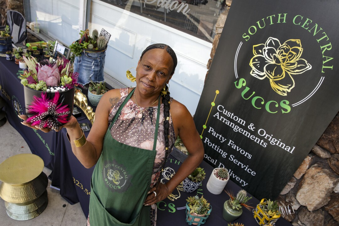 La Nola Smith holds a succulent arrangement while standing in front of her sales table that holds more arrangements.