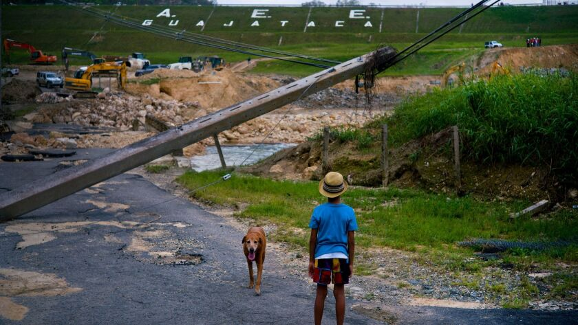 A boy watches the repairs of Guajataca Dam, which cracked during Hurricane Maria, in Quebradillas, Puerto Rico. Experts said the island could face nearly two decades of further economic stagnation and a steep drop in population as a result of Maria.