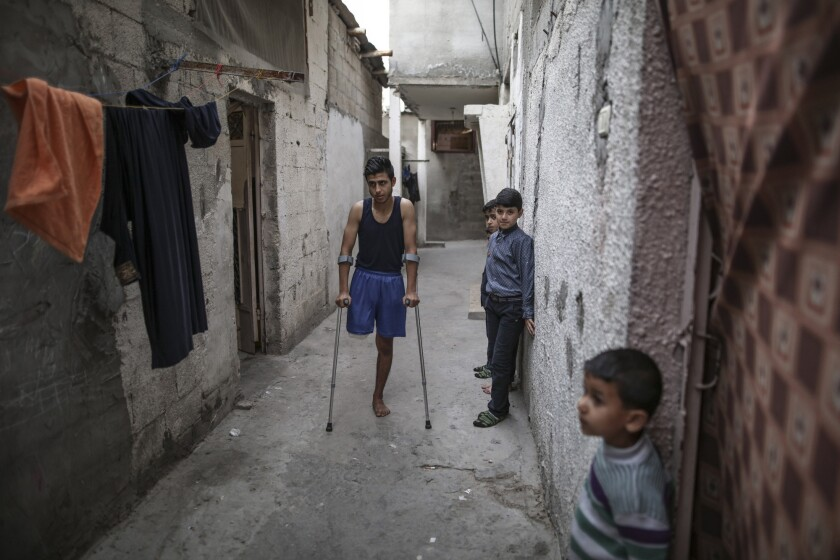 Mohammad al-Ajouri, 17, stands on crutches April 18, 2018, outside his family home in the Jabalya refugee camp in the northern Gaza Strip. His leg was struck by an Israeli soldier's bullet during recent demonstrations along the Gaza border.