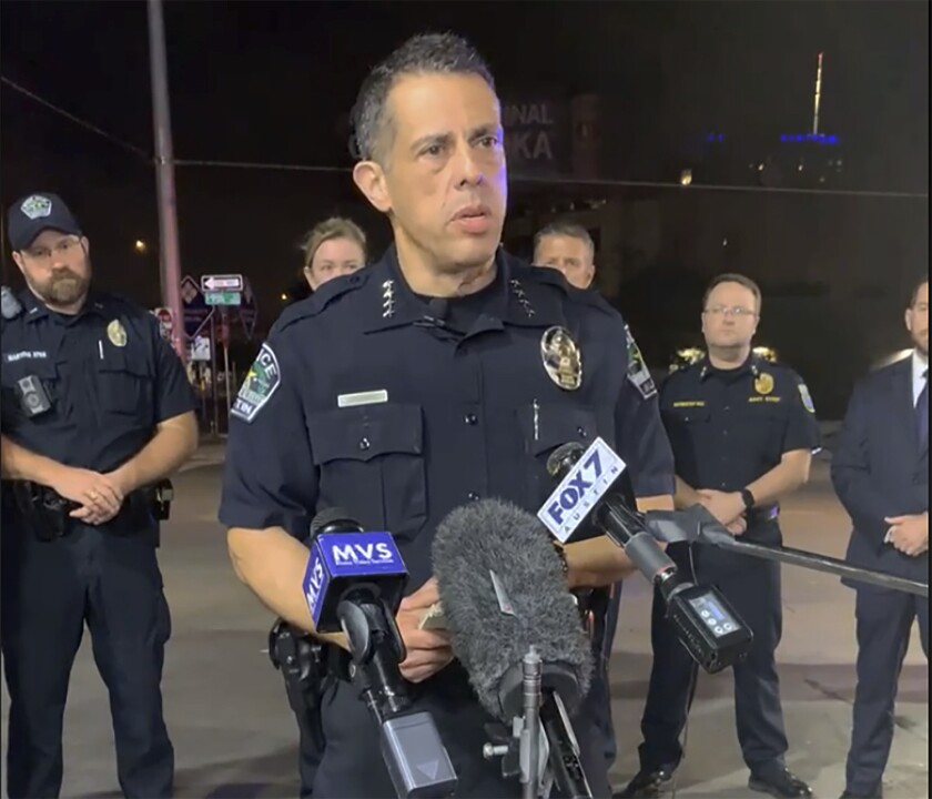 Police Chief Joseph Chacon speaks in front of microphones with several officers behind him