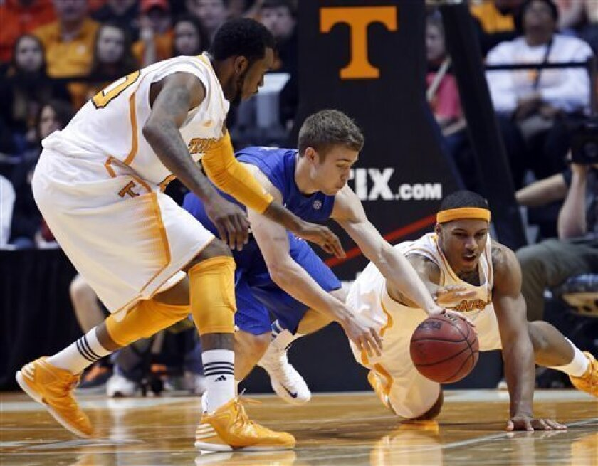 Tennessee forward Jarnell Stokes, right, dives for the ball as he battles with Kentucky guard Jarrod Polson, center, and forward Kenny Hall (20) in the first half of an NCAA college basketball game on Saturday, Feb. 16, 2013, in Knoxville, Tenn. (AP Photo/Wade Payne)