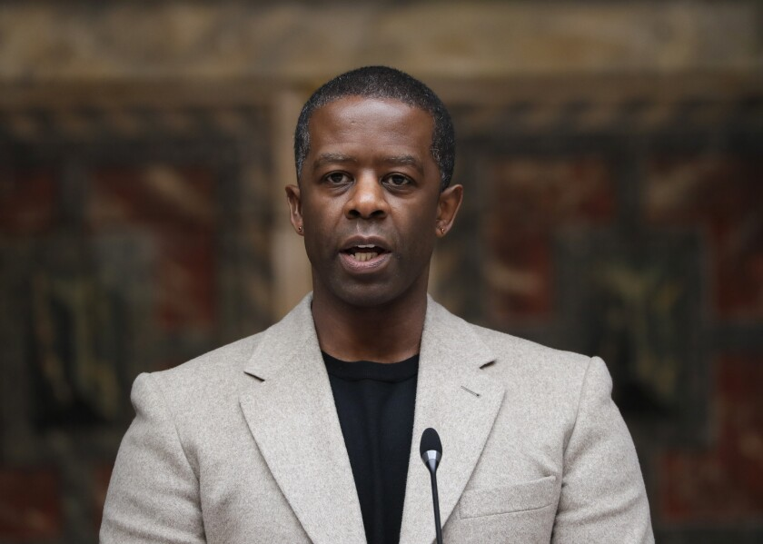 """FILE - In this May 10, 2021 file photo, British actor Adrian Lester speaks on stage at the official signing in ceremony for Sadiq Khan as the Mayor of London at Shakespeare's Globe Theatre in London. """"The Lehman Trilogy"""" was able to make only four preview performances on Broadway before the pandemic shut its doors. Now it plans to return to tell the story of an American financial giant's downfall with a new cast member. Stefano Massini's play about what led to the collapse of Lehman Brothers — adapted by Ben Power and directed by Sam Mendes — will add Adrian Lester, replacing Ben Miles, and joining Simon Russell Beale and Adam Godley. (AP Photo/Kirsty Wigglesworth, File)"""