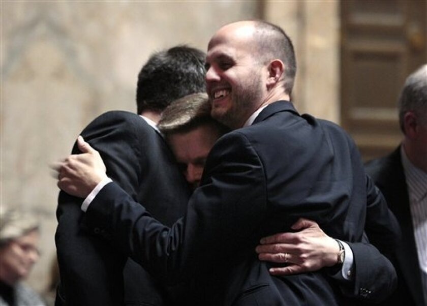Rep. Jamie Pedersen, D-Seattle, center, is congratulated by Dave Upthegrove, D-Des Moines, left, and Drew Hansen, D-Kitsap County, after the House voted to legalize gay marriage in Washington state Wednesday, Feb. 8, 2012, in Olympia, Wash. The action comes a day after a federal appeals court declared California's ban on same-sex marriage unconstitutional, saying it was a violation of the civil rights of gay and lesbian couples. Gregoire is likely to sign the bill next week. (AP Photo/Elaine Thompson)