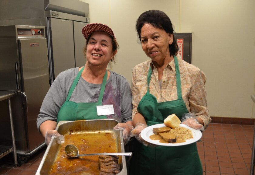 Volunteers Juliette Shamieh (left) and Margarita Casdellanos proudly serve up food.