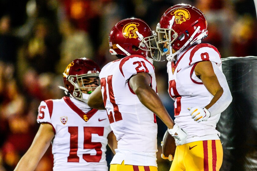 USC's Amon-ra St. Brown (8) is congratulated by teammate Tyler Vaughns (21) and Drake London (15) after scoring a first-quarter touchdown.