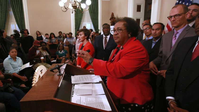 Assemblywoman Shirley Weber (D-San Diego), center, listens to a question during a news conference announcing her bill on police prosecutions Tuesday in Sacramento.