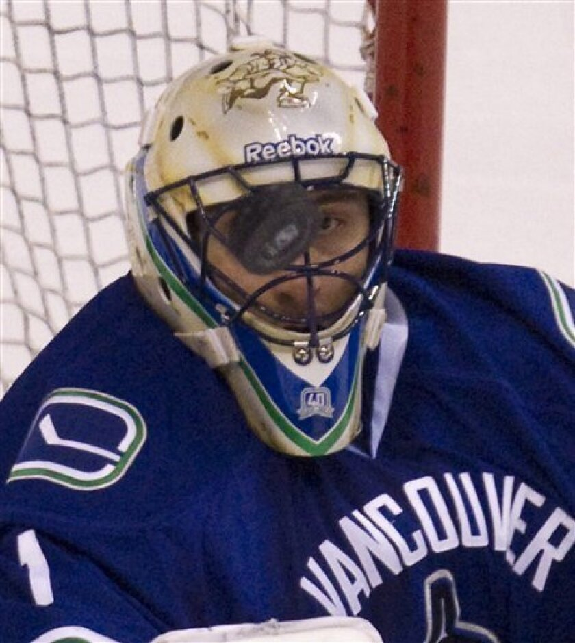Vancouver Canucks goalie Roberto Luongo (1) keeps his eye on the puck during second period NHL hockey action against the Los Angeles Kings at Rogers arena in Vancouver, British Columbia, Thursday, March 31, 2011.  (AP Photo/The Canadian Press, Jonathan Hayward)