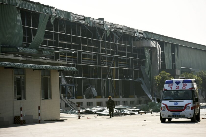 In this photo released by China's Xinhua News Agency, an ambulance waits outside the site of a gas explosion at the Fuhua Engineering and Manufacturing Co. factory in Foshan city, south China's Guangdong Province Wednesday, Dec. 31, 2014. (AP Photo/Xinhua, Liang Xu) NO SALES