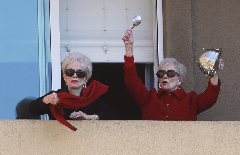 Joyce Kriesmer, 91, bangs a colander as she and her identical twin sister Jackie Voskamp waves a scarf on their balcony at the Vi at La Jolla Village senior living complex in La Jolla on Wednesday. Every weekday afternoon, the high-rise complex hosts a balcony pep rally for its residents who are sheltering in place because of the COVID-19 pandemic.