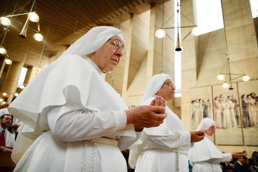 Sister Pilar, left, Sister Victorina and Mother Angelica hold out their hands to be blessed Sunday during a White Mass at the Cathedral of Our Lady of the Angeles. An annual tradition since 2009, the event has outgrown several local churches that once hosted the mass. Sunday was the first time it was held at the L.A. cathedral.