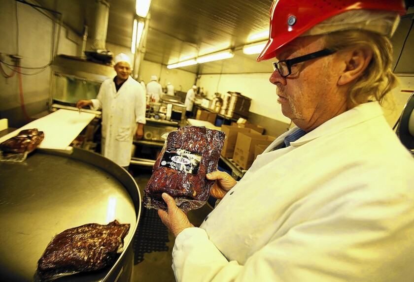Jerry Haines, general manager of R.C. Provision in Burbank, holds pastrami that's ready for shipping. The company, which supplies Pink's, Langer's Delicatessen and other eateries, is struggling as beef prices have hit a record high in the U.S.