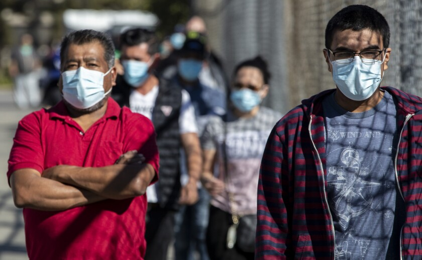 People wait in line Tuesday at a walk-up COVID-19 testing site in San Fernando.
