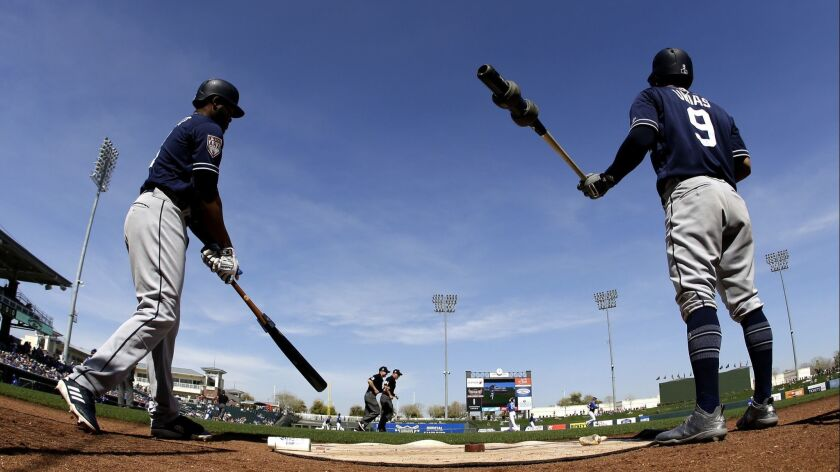 San Diego Padres' Manuel Margot, left, and Luis Urias warm up before a spring training baseball game