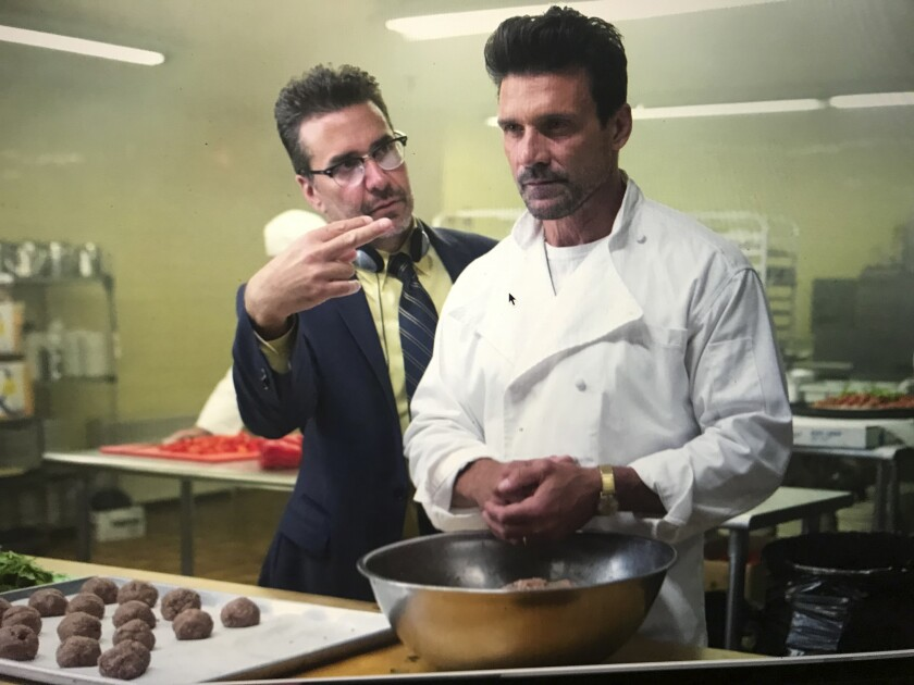 """This image released by Universal Pictures shows writer-director James DeMonaco, left, with actors Frank Grillo during the filming of """"This is the Night,"""" available on video-on-demand. (KC Bailey/Universal Pictures/Blumhouse via AP)"""