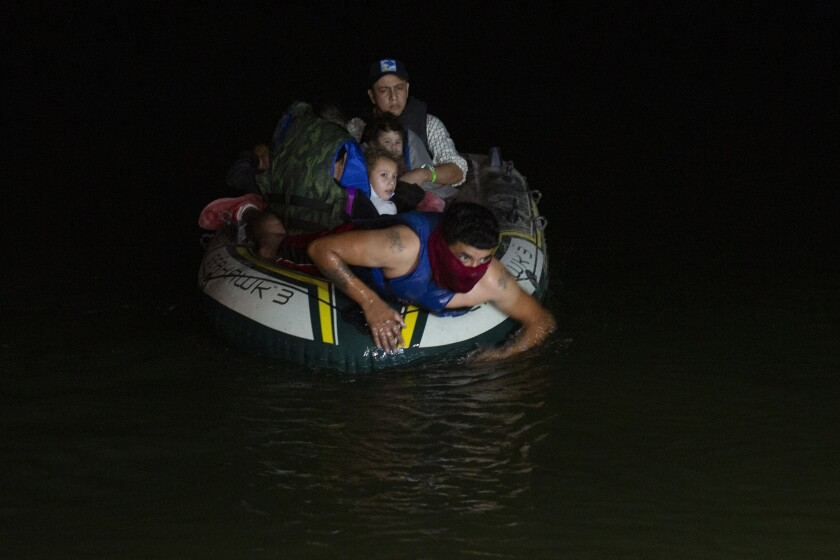 A smuggler takes migrants, mostly from Central American countries, on a small inflatable raft towards U.S. soil