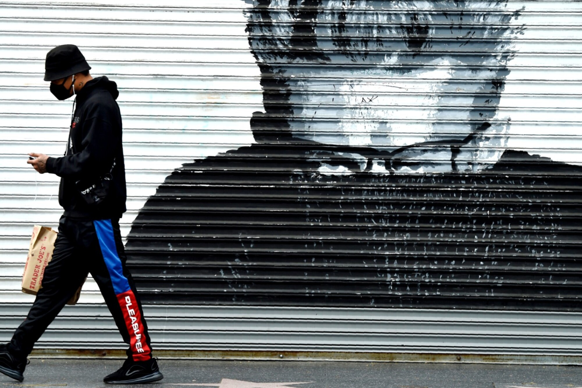 A shopper walks past a storefront mural depicting actor James Dean in Los Angeles on Tuesday.