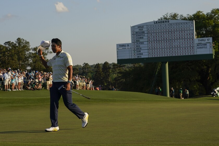 Hideki Matsuyama, of Japan, waves his cap after winning the Masters golf tournament on Sunday, April 11, 2021, in Augusta, Ga. (AP Photo/David J. Phillip)
