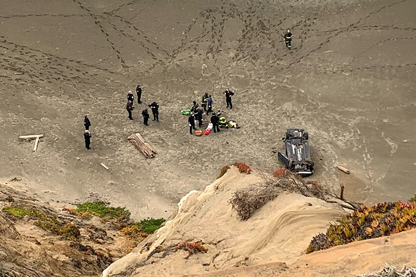 From the top of a cliff, a car is seen upside down in sand, with about a dozen firefighters nearby.